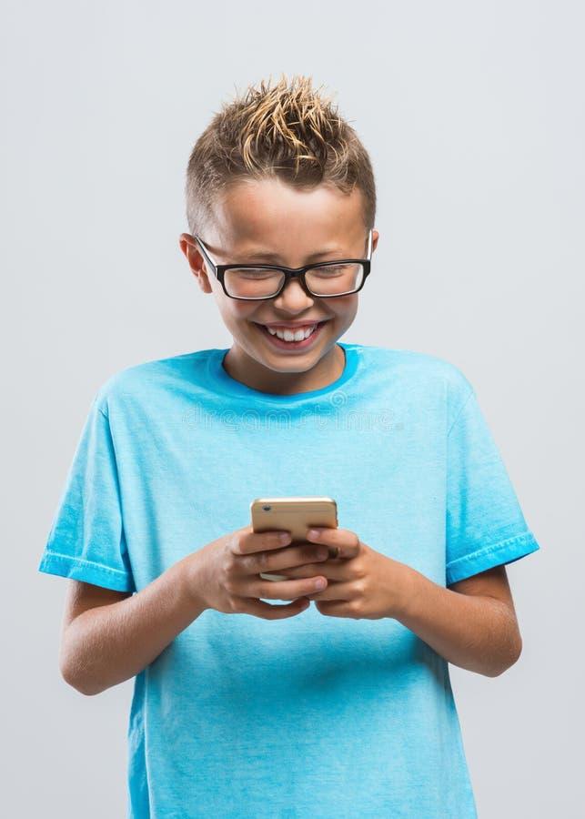 使用与他巧妙的电话的男孩 库存图片