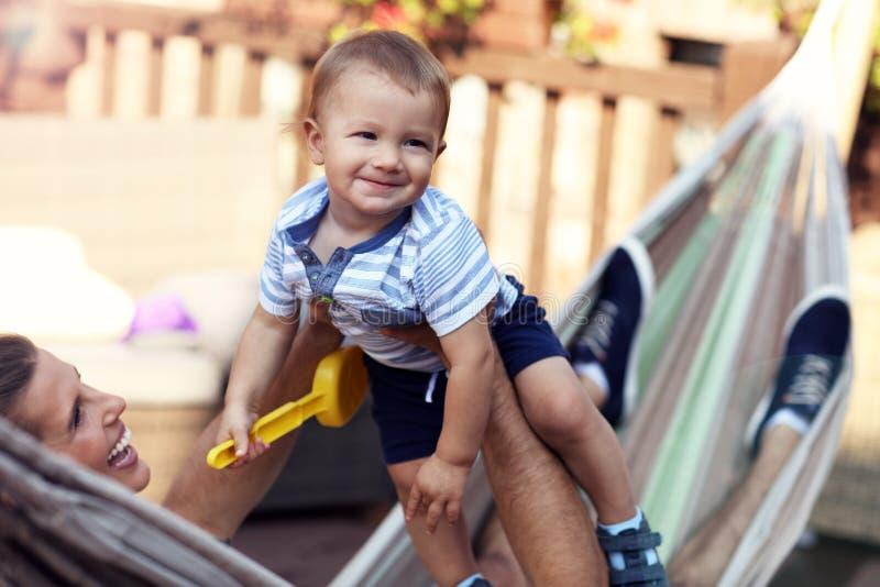 使用与他们的吊床的男婴的愉快的父母 免版税库存照片