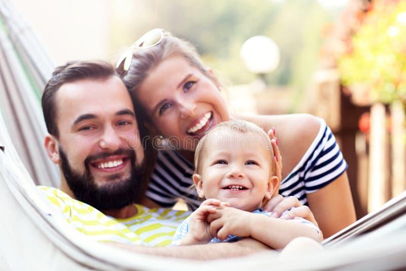 使用与他们的吊床的男婴的愉快的父母 库存图片