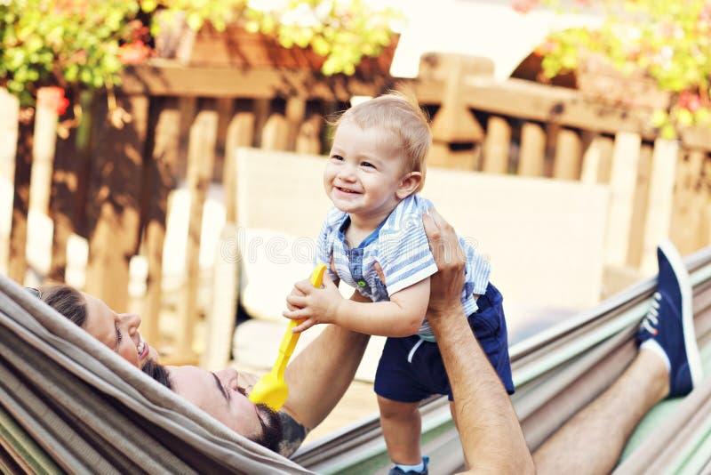 使用与他们的吊床的男婴的愉快的父母 免版税库存图片