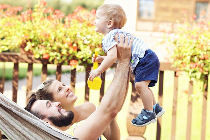 使用与他们的吊床的男婴的愉快的父母 库存照片