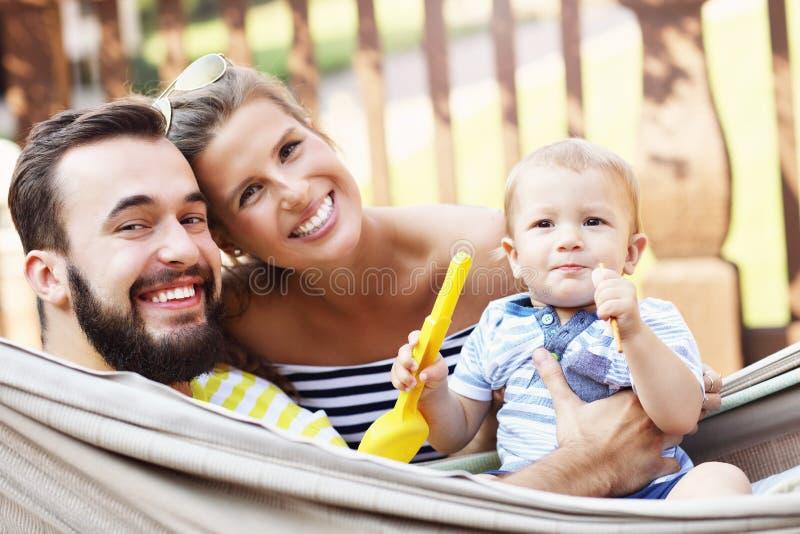 使用与他们的吊床的男婴的愉快的父母 图库摄影