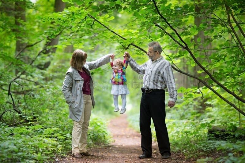 使用与他们的小孙女的年轻祖父母 免版税库存图片