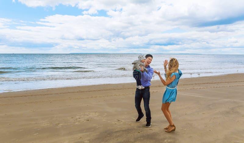 使用与他的海滩的儿子的父母 免版税库存图片
