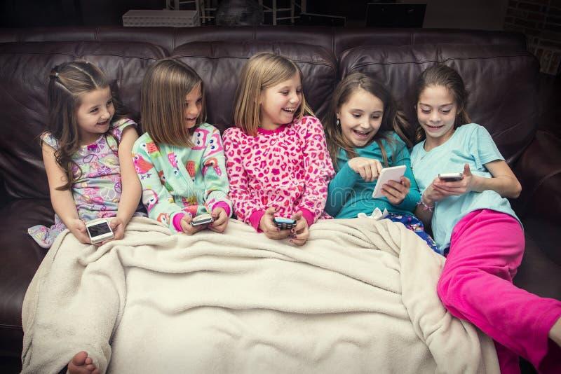 使用与他们的电子移动设备的小组小女孩 免版税图库摄影