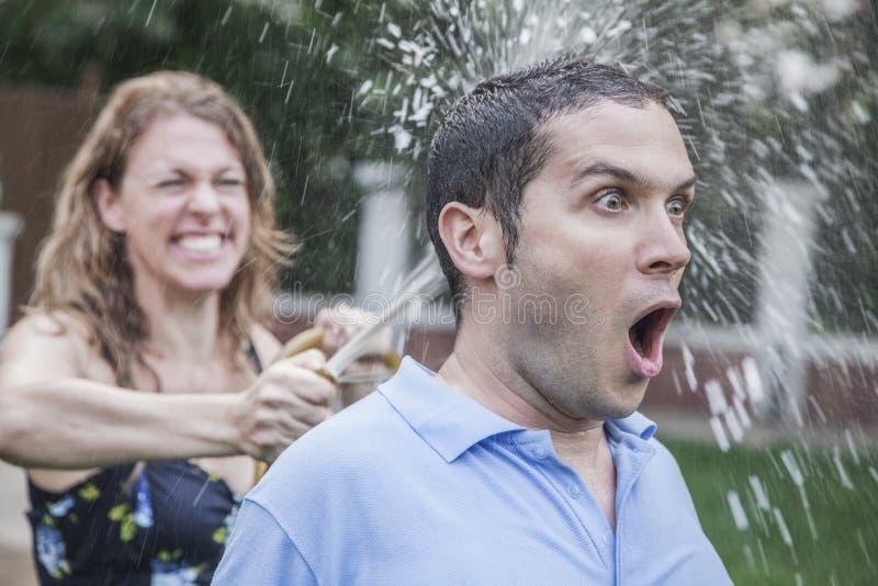 使用与水管和喷洒的夫妇外面在庭院,人看一看震惊,特写镜头 库存照片