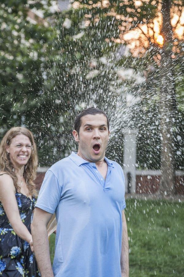 使用与水管和喷洒的夫妇外面在庭院,人看一看震惊  免版税库存照片