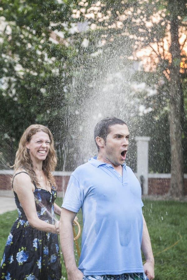 使用与水管和喷洒的夫妇外面在庭院,人看一看震惊  库存图片