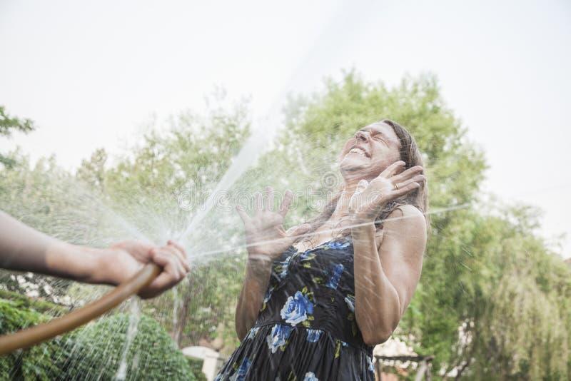 使用与水管和喷洒的夫妇外面在庭院,妇女设法保护自己 免版税图库摄影