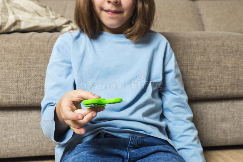 使用与绿色坐立不安锭床工人玩具的小女孩 库存图片