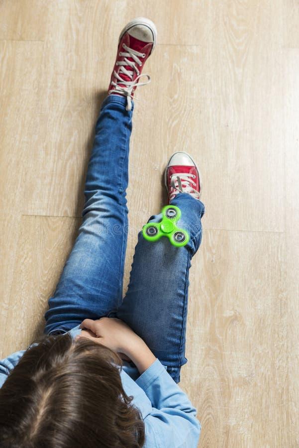 使用与绿色坐立不安锭床工人玩具的小女孩 图库摄影