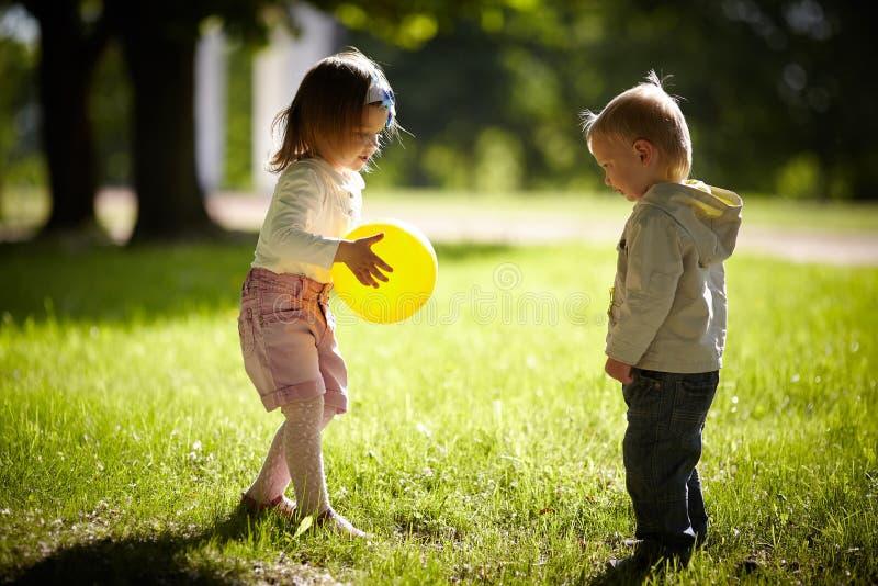 使用与黄色球的男孩和女孩 免版税图库摄影