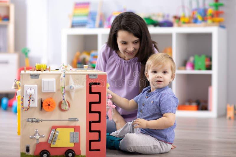 使用与busyboard的逗人喜爱的小孩婴孩 儿童` s教育玩具 免版税库存图片