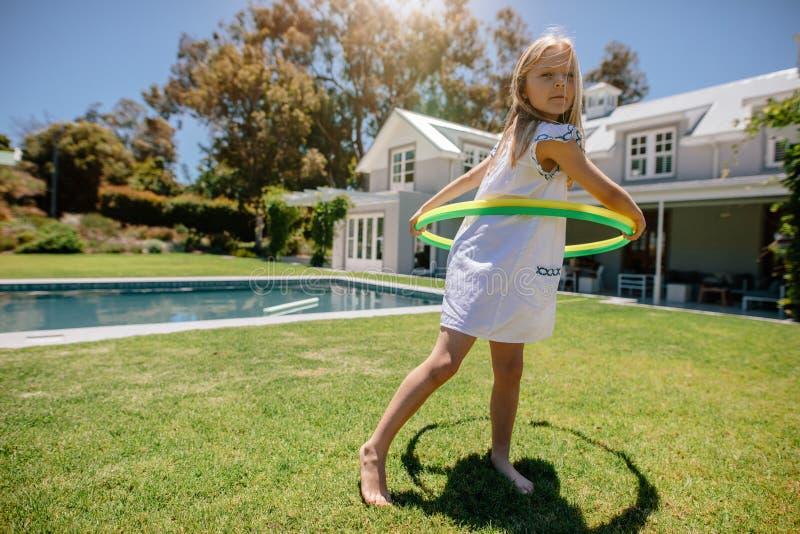 使用与hula箍的逗人喜爱的小女孩在后院 免版税库存图片