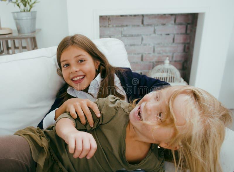 使用两个逗人喜爱的姐妹在家,房子内部的小女孩在沙发,弄乱头发,战斗与枕头,生活方式 免版税图库摄影