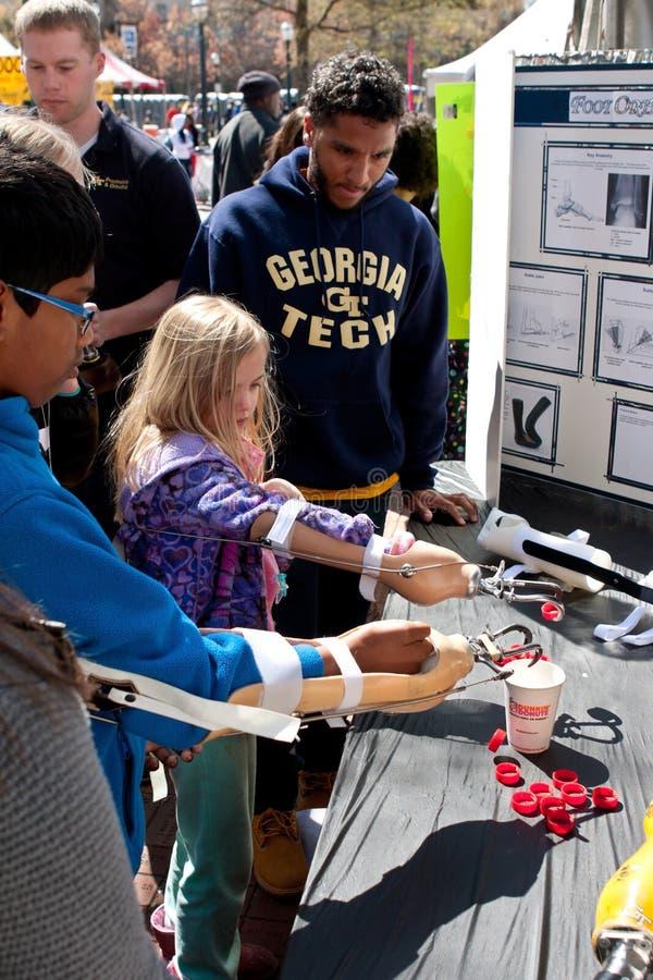 使用义肢胳膊的孩子实践在亚特兰大科学展览 免版税库存照片