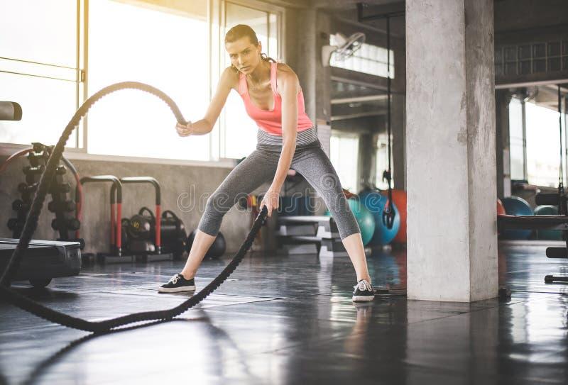 使用争斗绳索在健身房,在功能训练的女性做的锻炼的坚强的妇女 图库摄影