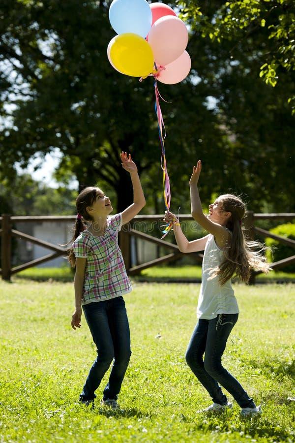 使用二个的小女孩户外 图库摄影