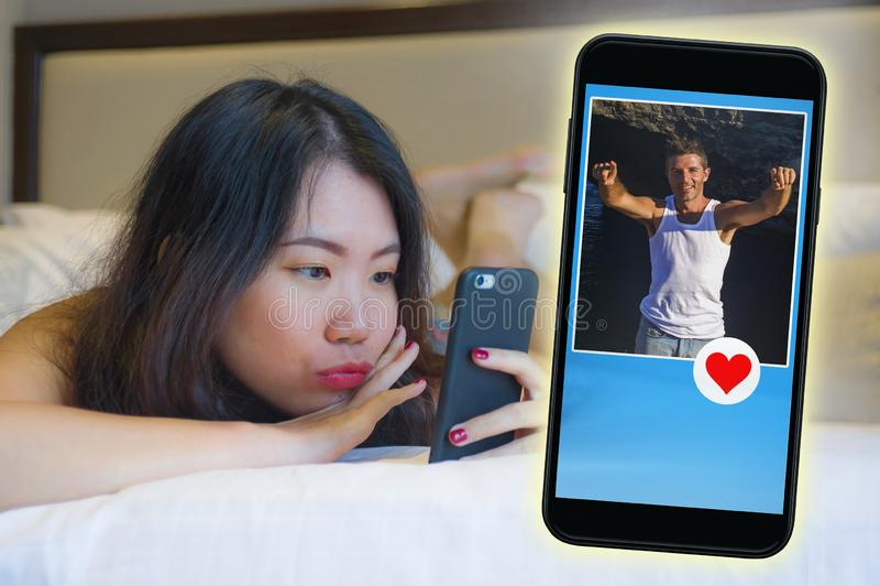 使用互联网在送象消息的手机的网上约会的app的年轻美丽和愉快的亚裔韩国女孩到英俊的Cauc 免版税库存照片