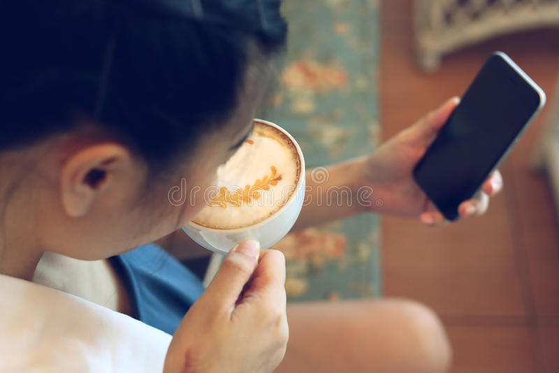 使用互联网手机技术的妇女在咖啡馆咖啡 库存照片