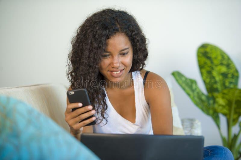 使用互联网手机的年轻愉快和美丽的黑人拉丁美洲的妇女生活方式画象,当研究膝上型计算机co时 免版税库存图片