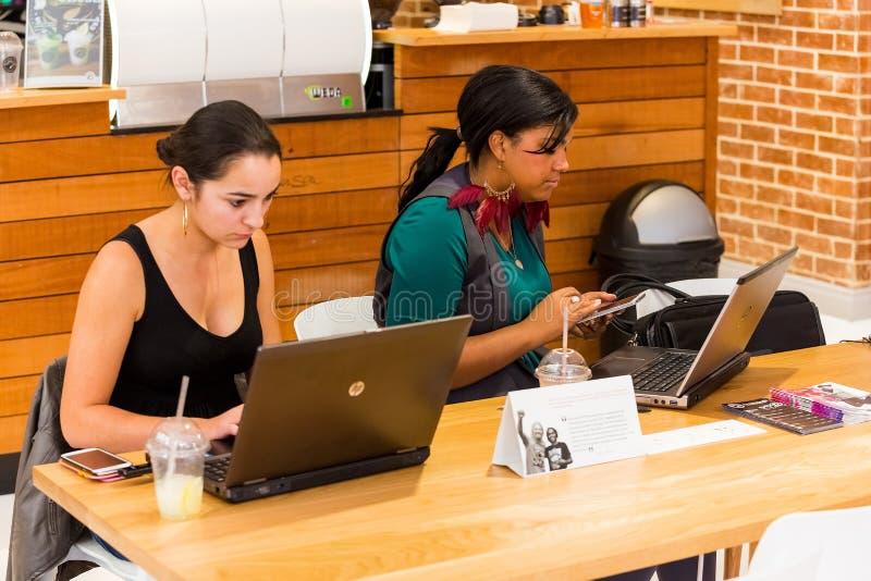 使用互联网的不同的女性顾客在咖啡馆 免版税库存照片