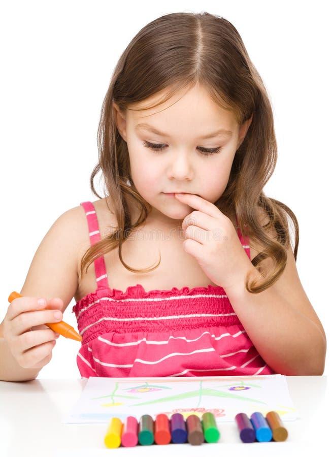 使用五颜六色的蜡笔,小女孩画 免版税库存图片