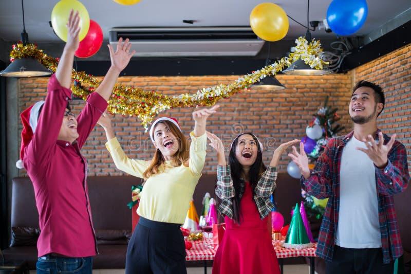 使用亚洲男人和女服圣诞老人的帽子获得乐趣在圣诞晚会,跳舞和在餐馆迅速增加, 免版税图库摄影