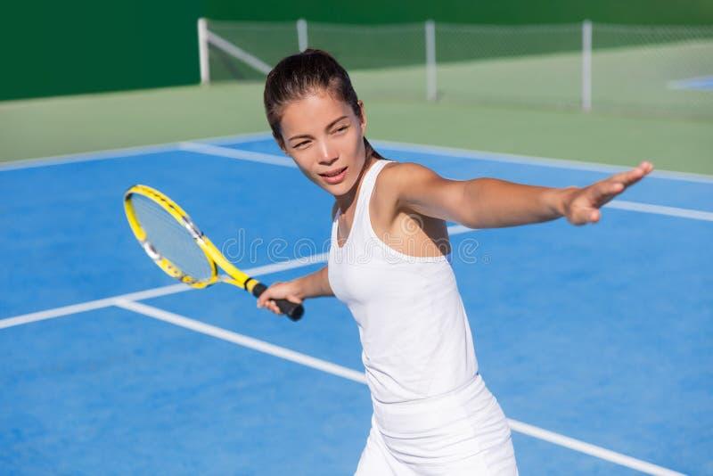 使用亚裔网球员的妇女击中正手击球 免版税库存图片