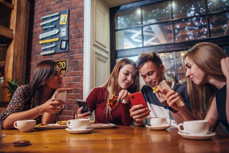 使用他们的手机的青年人坐在桌附近有膳食在现代时髦的咖啡馆 免版税库存照片