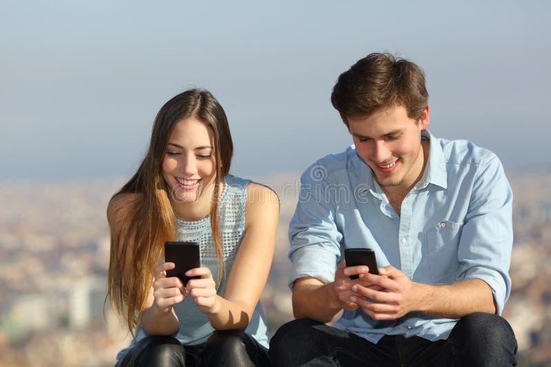 使用他们的智能手机的愉快的夫妇外面 库存照片