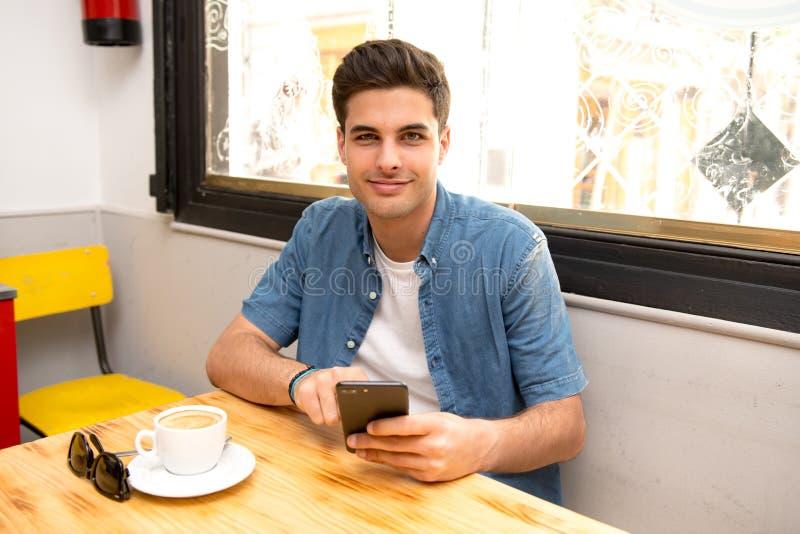 使用他巧妙的电话的年轻学生读文本,当食用咖啡时 免版税库存照片