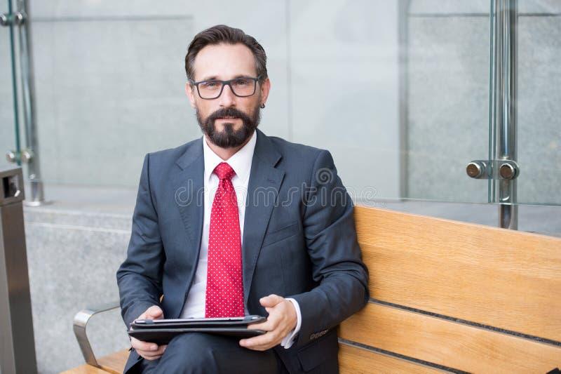 使用他的个人计算机片剂的商人,当坐长凳时 使用片剂计算机的资深商人,当等待他的汽车时 免版税库存图片