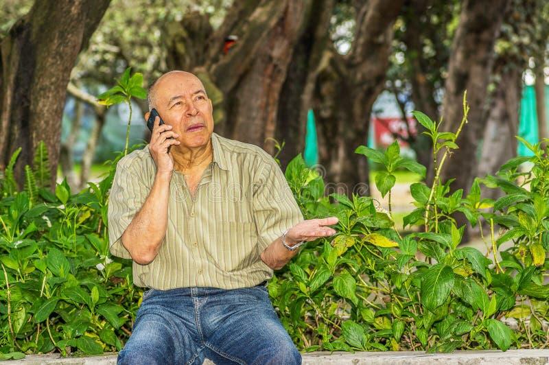 使用他的手机和享受自然,室外观点的老人坐长凳 被忘记的所有问题 免版税库存图片