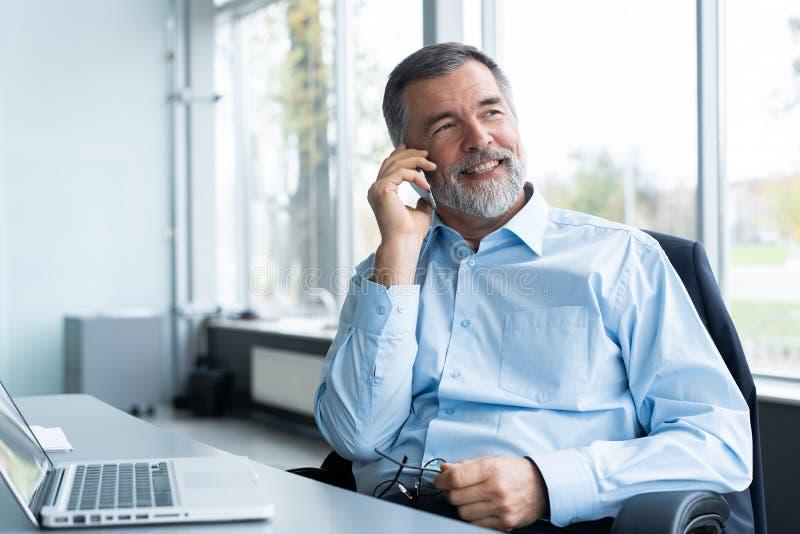 使用他的手机的行政资深商人和谈话与某人,当工作膝上型计算机在办公室时 免版税库存图片