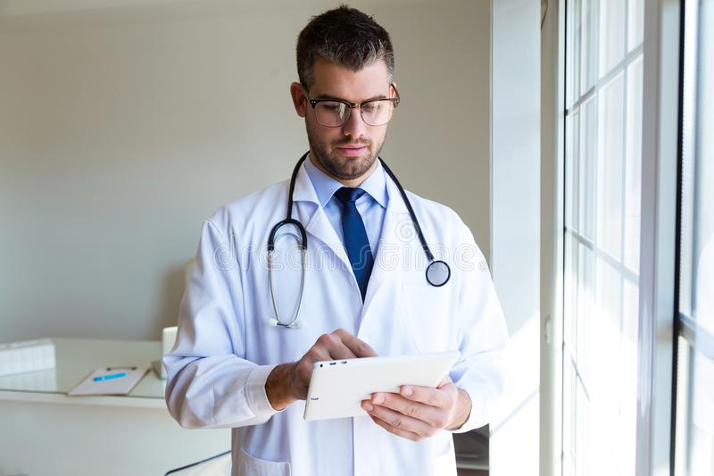使用他的数字式片剂的确信的男性医生在办公室 免版税库存图片
