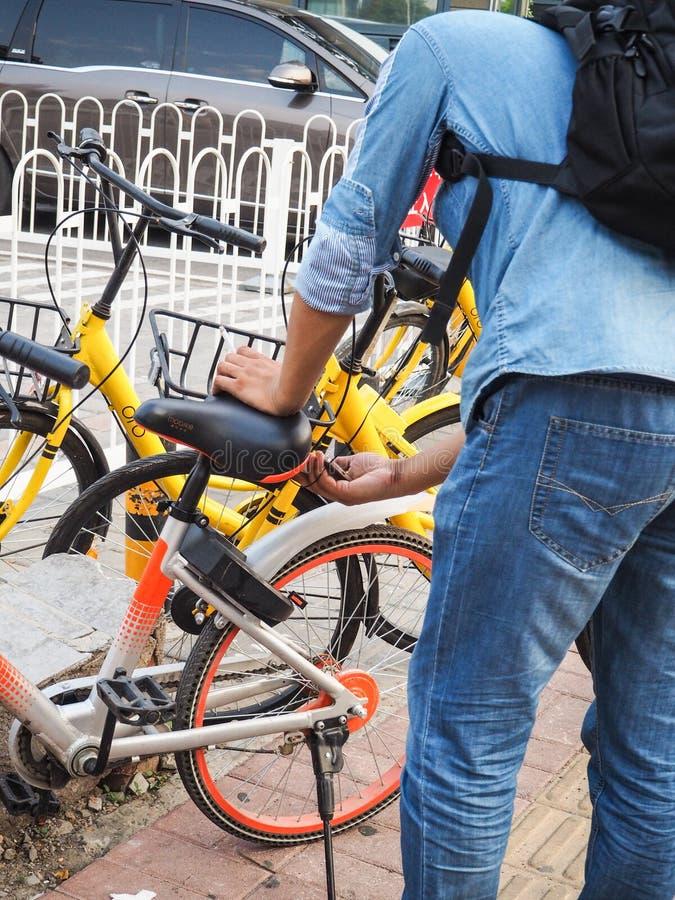 使用他的智能手机的年轻人打开一辆共有的自行车 免版税图库摄影