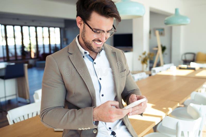 使用他的智能手机的英俊的年轻商人,当坐桌在办公室时 免版税库存照片