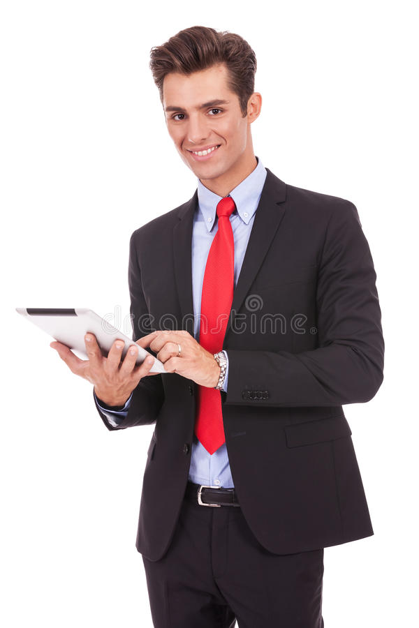 使用他的片剂填充的微笑的商人 库存照片
