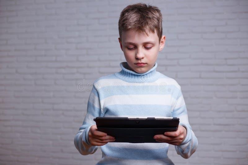 使用他的片剂的男小学生 技术和教育概念 免版税库存照片