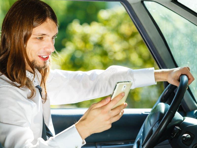 使用他的电话的人,当驾驶汽车时 免版税库存图片