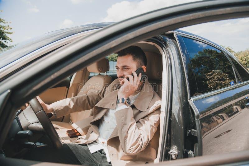 使用他的电话的英俊的商人在一辆现代汽车 库存图片