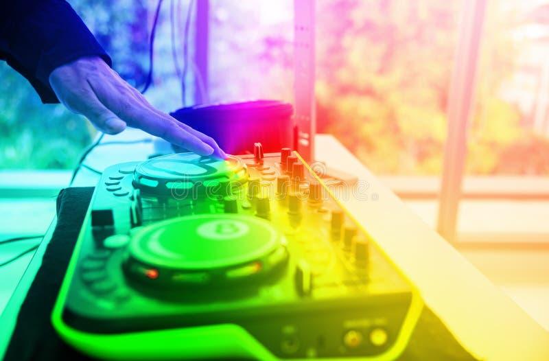 使用伴音系统的技术员的手混合在阶段的音响器材板与柔光 在党的DJ混合的声音在客栈和 免版税图库摄影