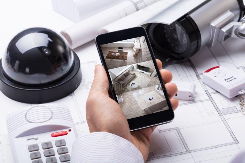 使用住家安全系统的人手在移动电话 免版税库存图片