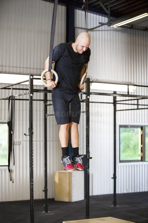 使用体操圆环的坚定的男性运动员在健身俱乐部 库存图片
