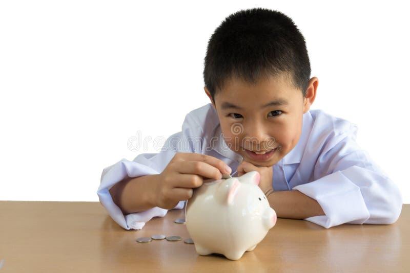 使用作为医生平衡金钱的亚裔男孩在存钱罐中 库存照片