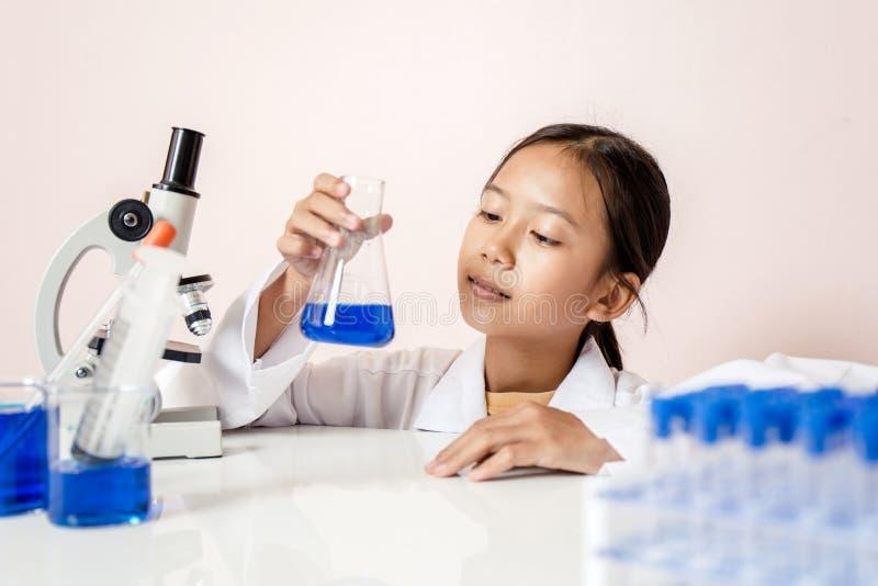使用作为科学家的亚裔女孩试验实验室设备 免版税库存照片