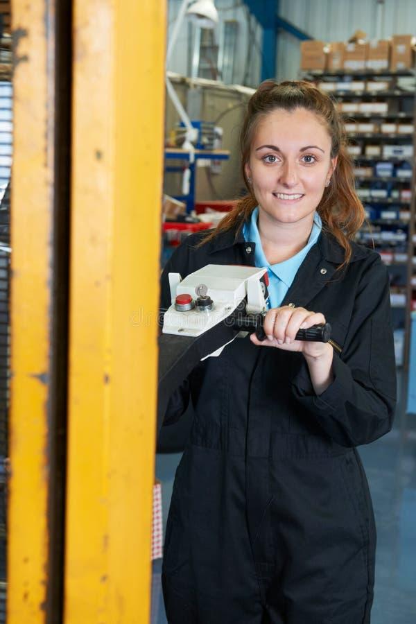 使用供给动力的铲车的女性工厂劳工装载物品 库存照片