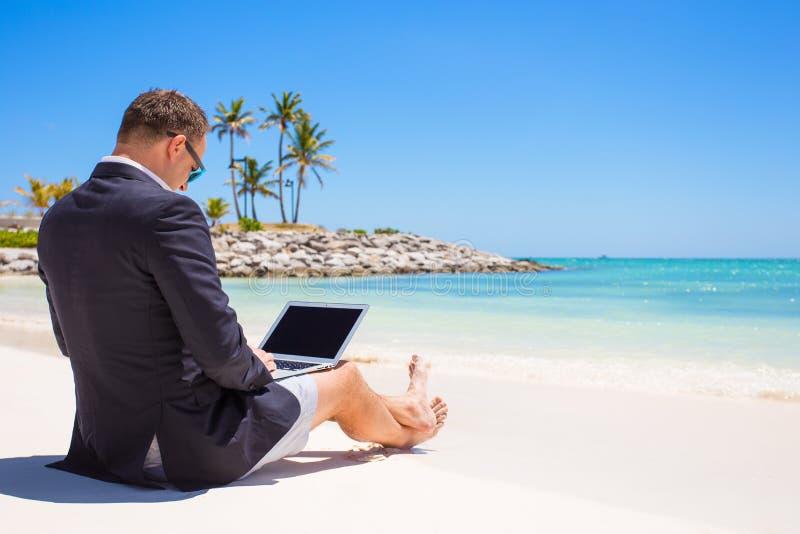 使用便携式计算机的商人在热带海滩 免版税库存图片