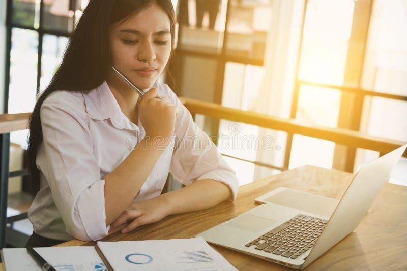 使用便携式计算机的女实业家在工作场所 年轻女性e 库存图片